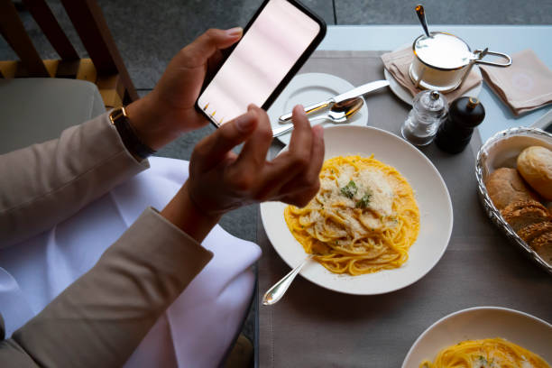 woman sitting in a restaurant and using her smart phone - expensive iphone on the table stock pictures, royalty-free photos & images