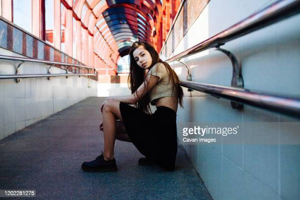 woman sitting in a tunnel with arches - bending over in skirt stock pictures, royalty-free photos & images