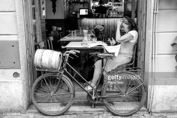a person reads the newspaper sitting in a typical trastevere restaurant in rome - vintage restaurant stock pictures, royalty-free photos & images
