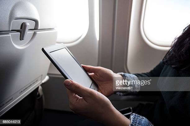 Woman sitting in airplane using E-Book, partial view