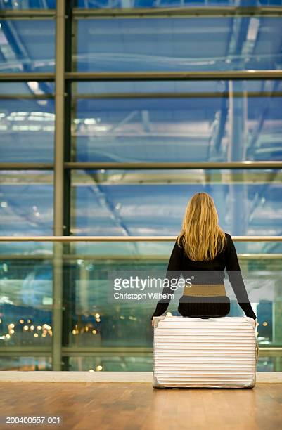 Woman sitting in airport, rear view