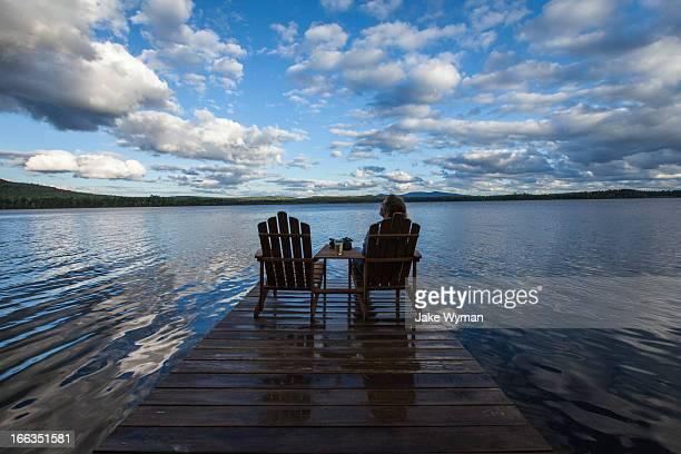 A woman sitting in an adirondack chair on a dock at Spencer Pond in northern Maine.