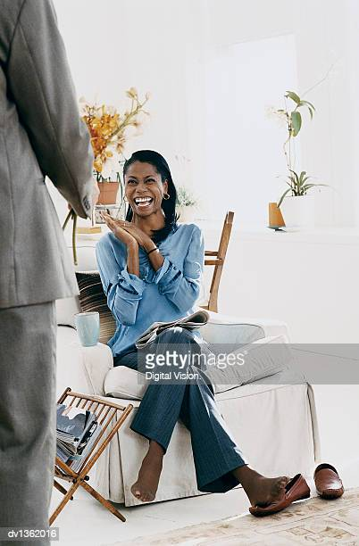 woman sitting in an armchair in her sitting room pleased at receiving a bouquet of orchids from a man - magazine rack stock photos and pictures