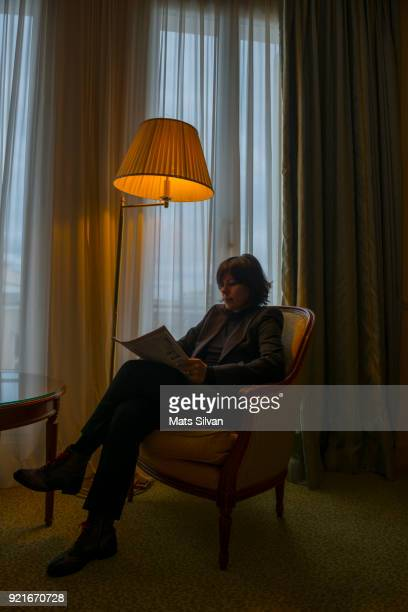 Woman Sitting in an Armchair with Floor Lamp and Reading the Newspaper