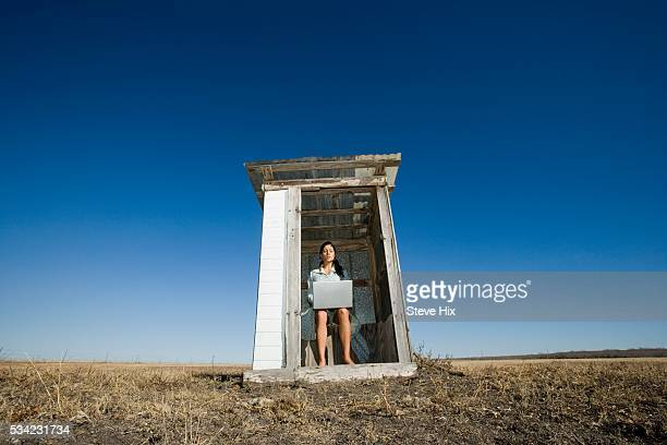 woman sitting in an outhouse, holding a laptop computer - human toilet stock-fotos und bilder