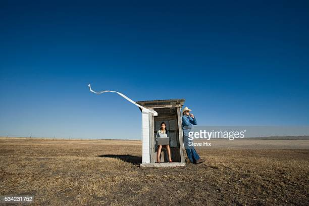 woman sitting in an outhouse with man leaning on it - human toilet stock-fotos und bilder