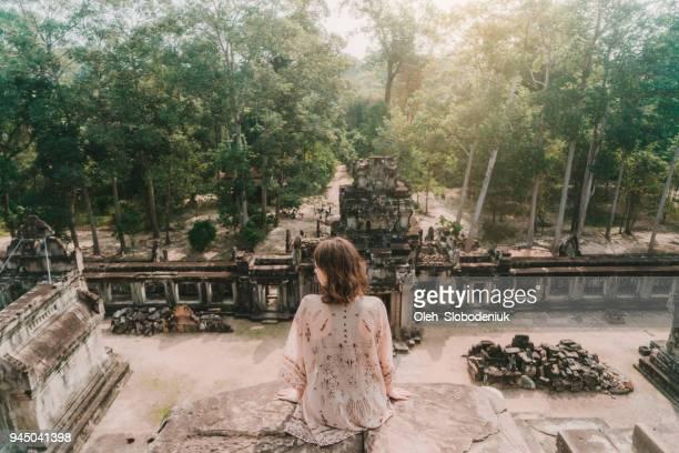 カンボジアのアンコール寺院に座っている女性 - アンコールワット ストックフォトと画像