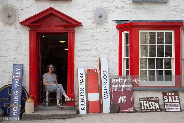 Woman sitting in antique shop doorway