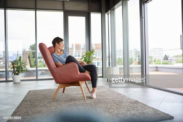 woman sitting in armchair at home looking out of balcony door - lounge chair stock pictures, royalty-free photos & images