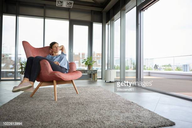 woman sitting in armchair at home relaxing - comfortabel stockfoto's en -beelden