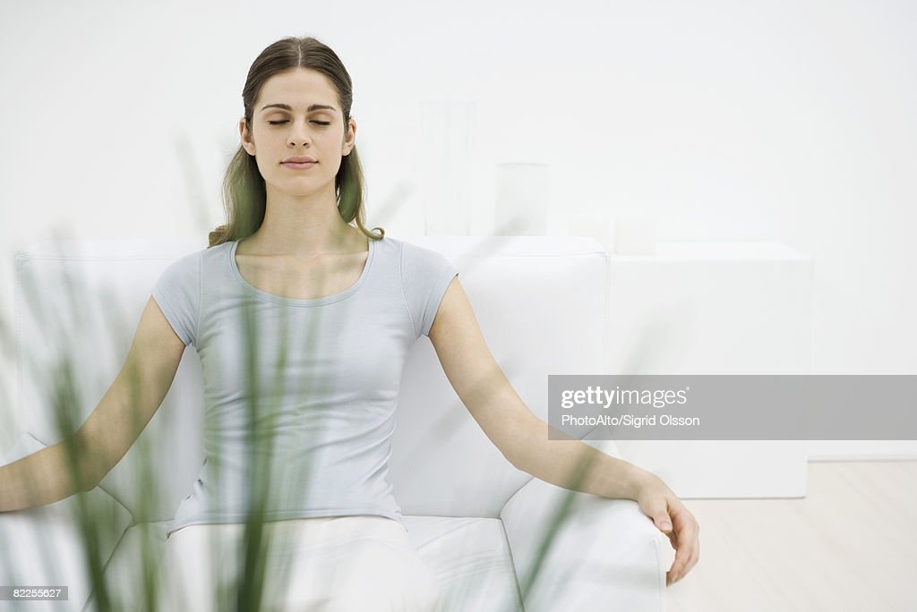 Woman sitting in armchair, eyes closed, plant in foreground : Stock Photo
