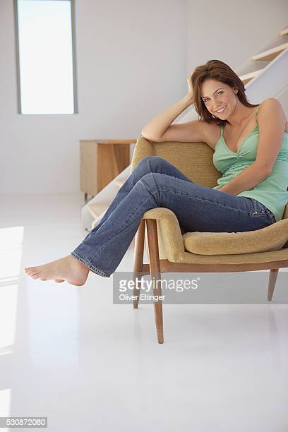 woman sitting in armchair in loft - oliver eltinger stock-fotos und bilder