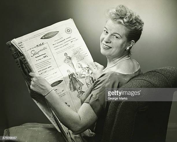 woman sitting in armchair, reading newspaper, smiling, (b&w) - 20th century stock pictures, royalty-free photos & images