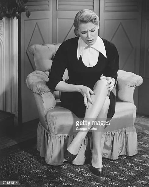 Mujer sentada en un sillón mientras ve las piernas (B & P