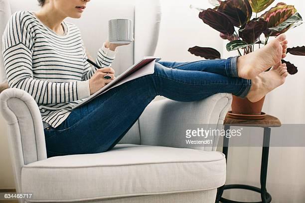 woman sitting in armchair writing on notepad - adulto de mediana edad fotografías e imágenes de stock