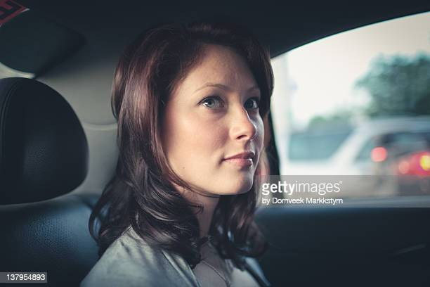 Woman sitting in back seat of car
