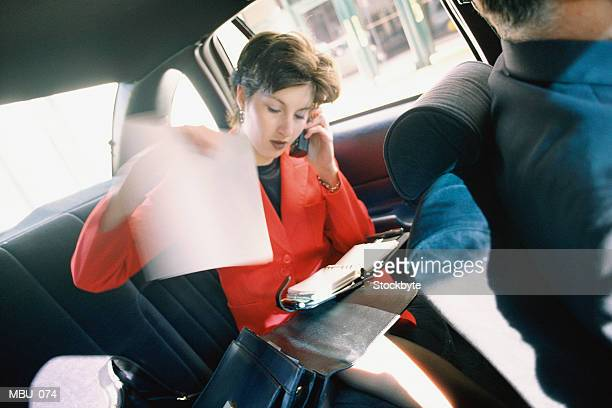 Woman sitting in back seat of vehicle, talking on cellular phone
