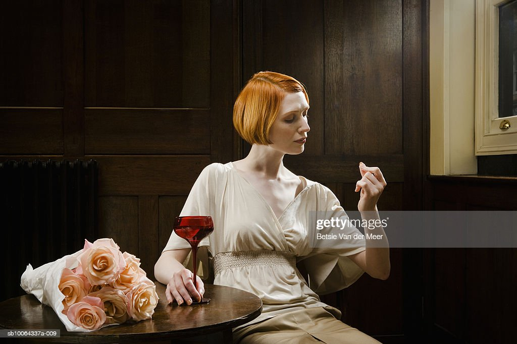 Woman sitting in bar with martini, looking at fingernails : Stock Photo