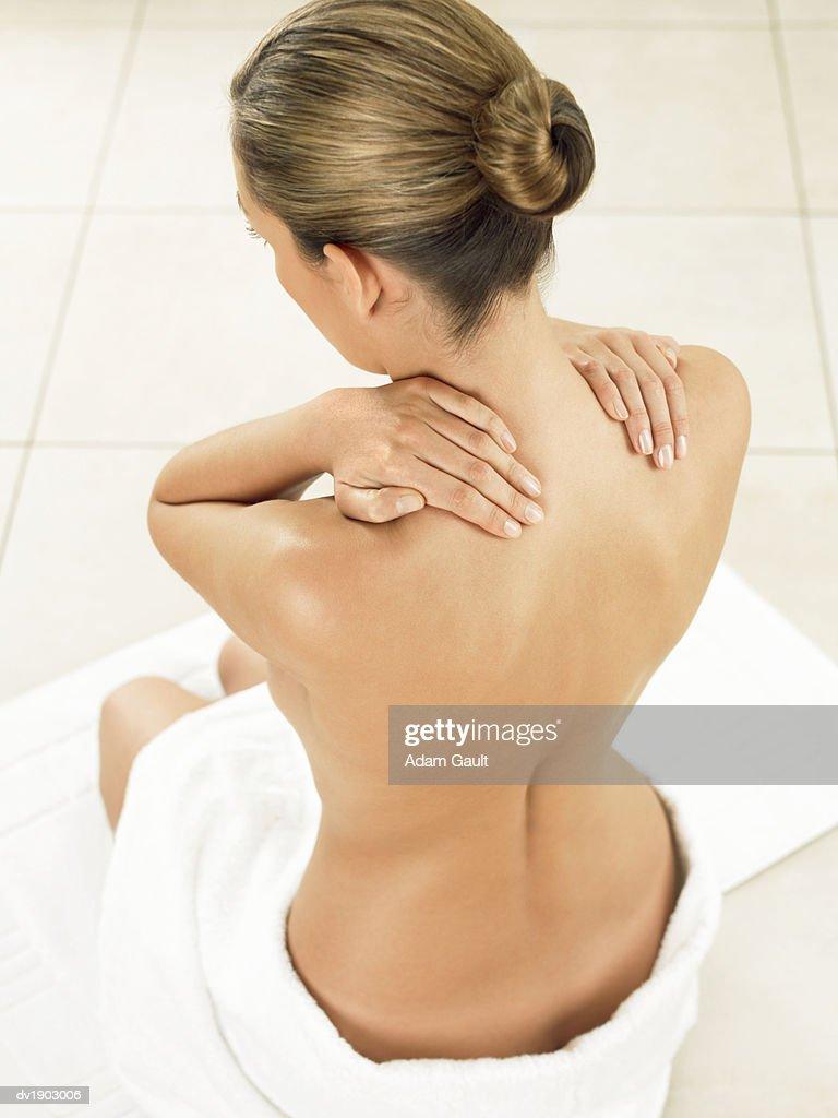 Woman Sitting in Bathroom Massaging Her Neck : Foto de stock