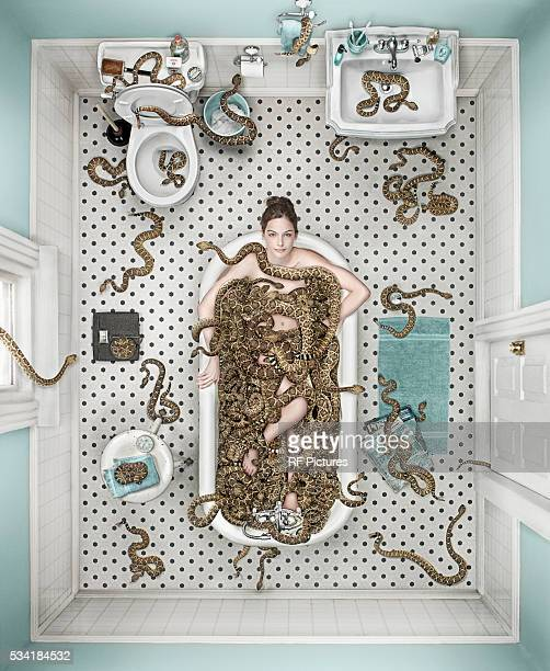 Woman sitting in bathtub with rattlesnakes