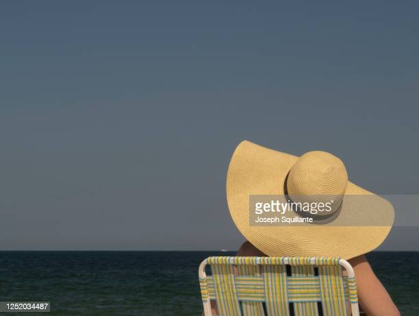 woman sitting in beach chair in straw hat - joseph squillante stock pictures, royalty-free photos & images