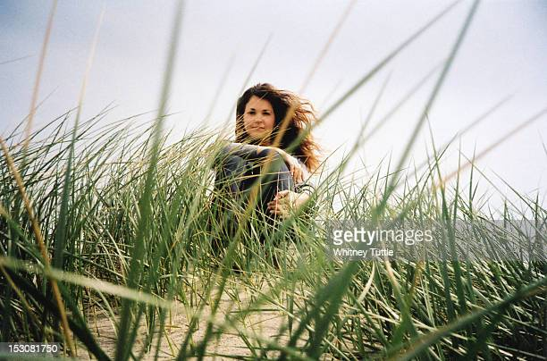 woman sitting in beach grass - manzanita stock pictures, royalty-free photos & images