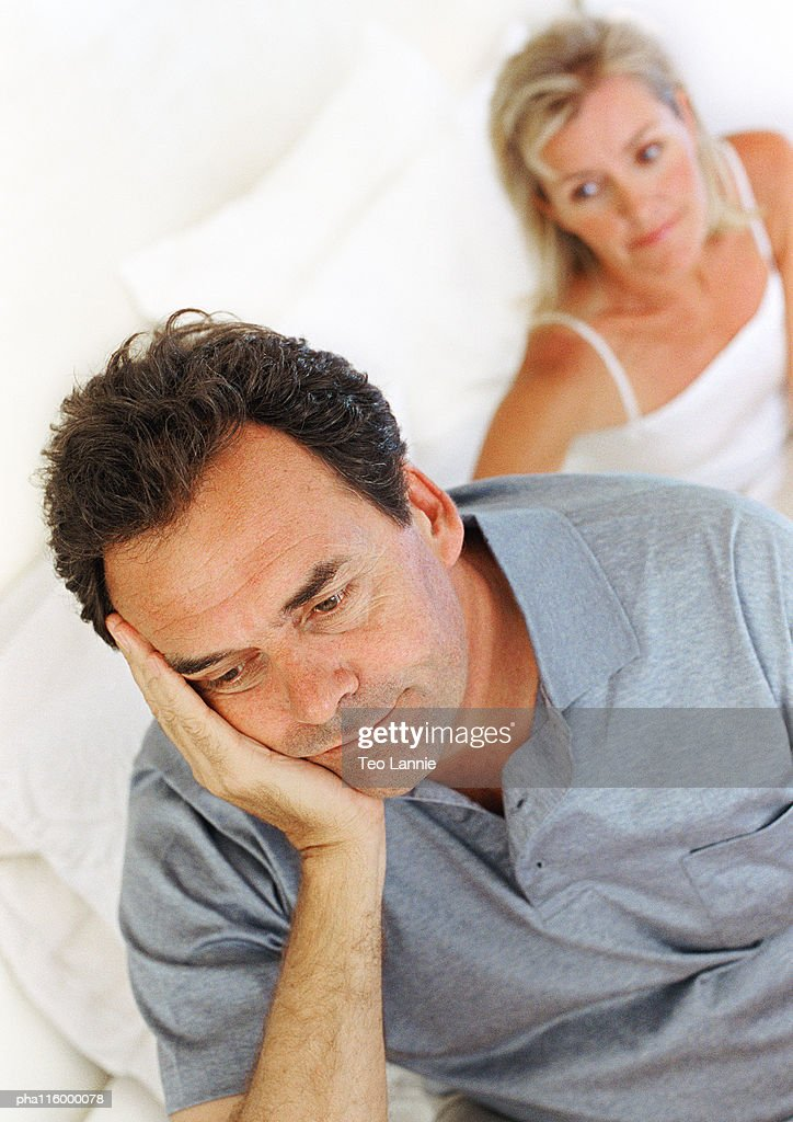 Woman sitting in bed behind man with hand on cheek : Stockfoto
