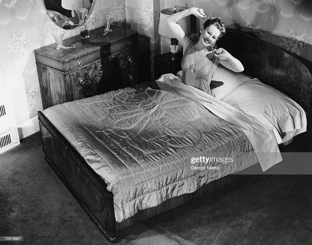 Woman sitting in bed stretching : News Photo