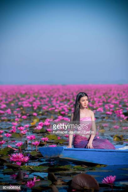 Woman Sitting In Boat Amidst Pink Flowers On Lake