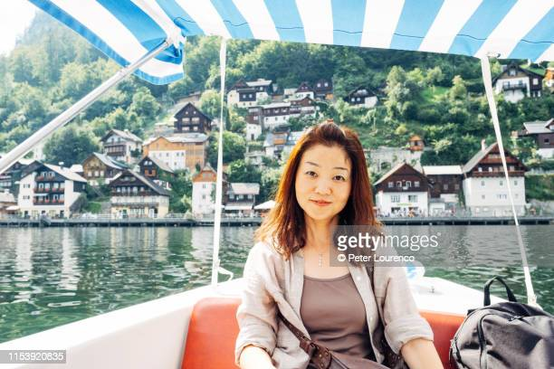 woman sitting in boat at hallstatt - peter lourenco stock pictures, royalty-free photos & images