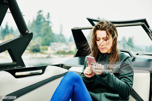 Woman sitting in boat looking at smartphone after early morning wakeboarding session