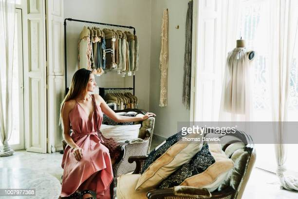 woman sitting in boutique admiring dress on mannequin in window - pink dress stock pictures, royalty-free photos & images
