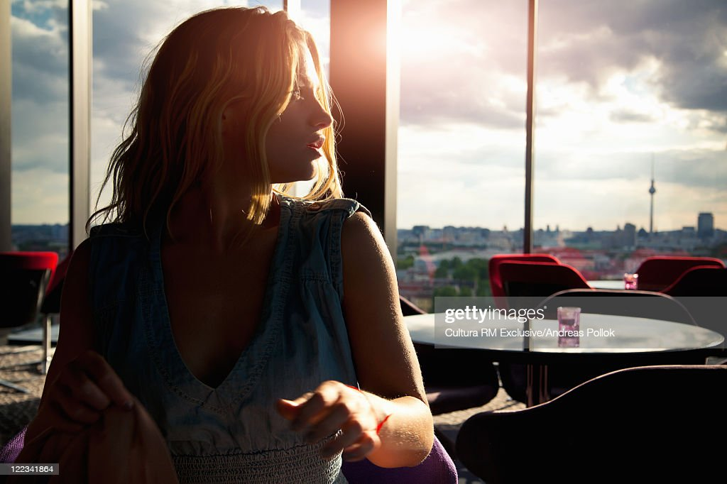 Woman Sitting In Cafe At Sunset High-Res Stock Photo