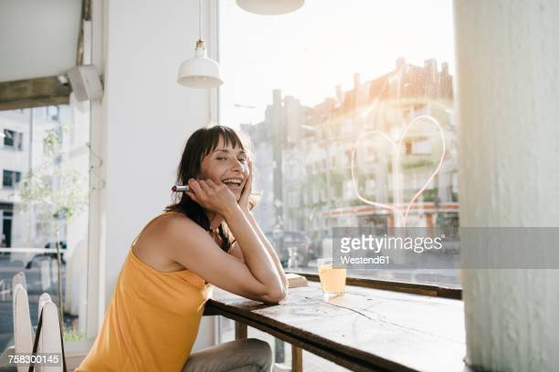 woman sitting in cafe drawing heart shape on window pane with lipstick - femme coquine photos et images de collection