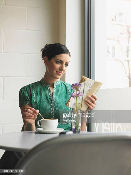 Woman sitting in cafe reading book while stirring cup with spoon