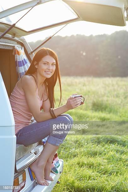 Woman sitting in camper van with hot drink.
