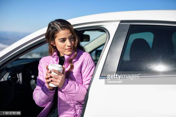 woman sitting in car having a hot coffee before skiing - hot spanish women stock pictures, royalty-free photos & images