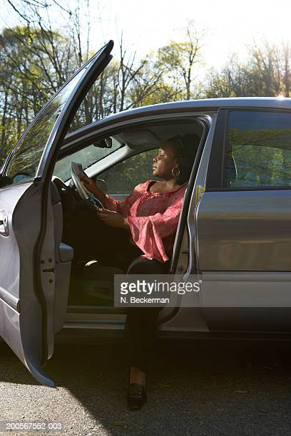 Woman sitting in car holding map