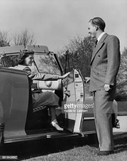 Woman sitting in car while man looking at her