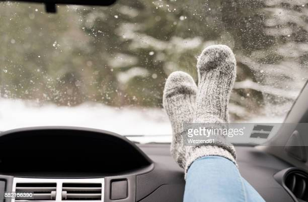Woman sitting in car with feet up on dashboard