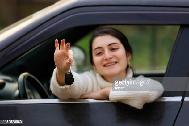woman sitting in car with key - domestic car stock pictures, royalty-free photos & images