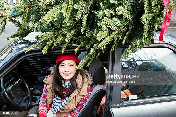 Woman sitting in car,Christmastree on top of car.