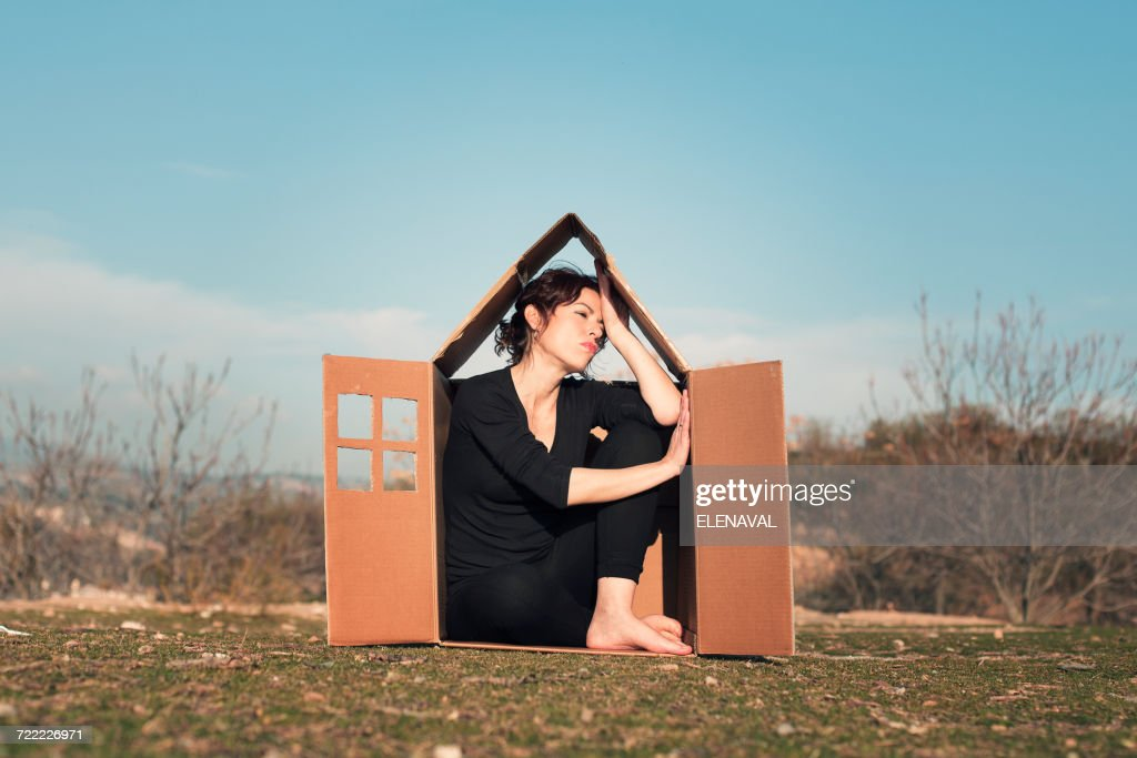 Woman sitting in cardboard box house : Stock Photo