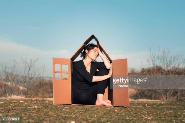 Woman sitting in cardboard box house