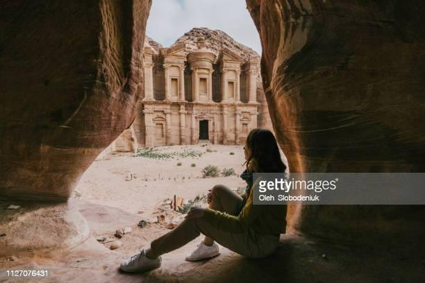 mujer sentada en la cueva y busca en el monasterio en petra - paisajes de jordania fotografías e imágenes de stock