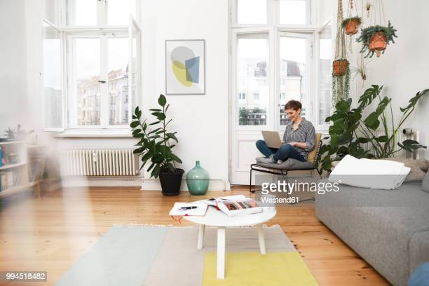 woman sitting in chair at home, using laptop - comfortabel stockfoto's en -beelden