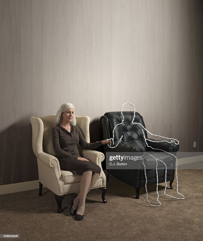 Woman sitting in chair holding hand of outlined male shape : Stock Photo