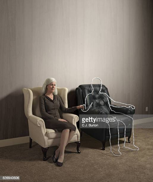 woman sitting in chair holding hand of outlined male shape - mourning stock pictures, royalty-free photos & images