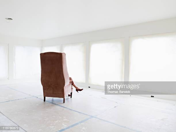 Woman sitting in chair in empty home