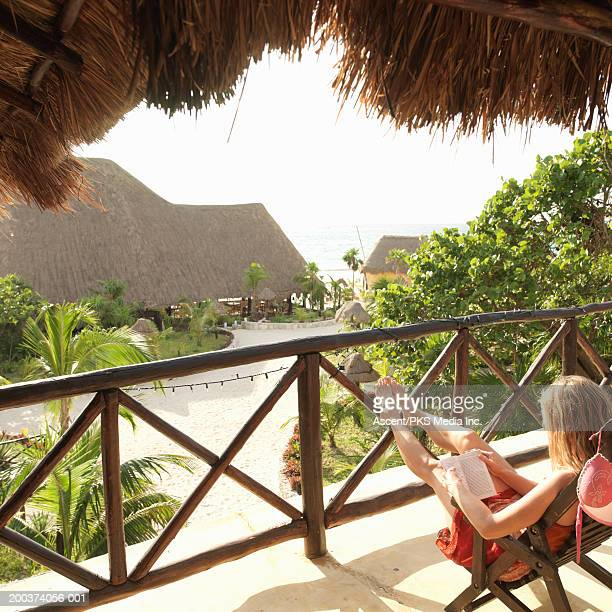 woman sitting in chair on balcony, reading book, rear view - mayan riviera stock photos and pictures